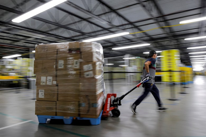 A worker pulls a cart piled high with Amazon packages through a warehouse