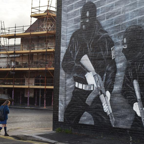 A schoolgirl walks past a loyalist paramilitary mural