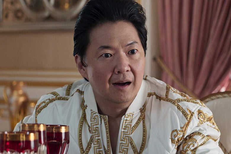Ken Jeong sits open-mouthed, his hair in a pompadour, wearing a white outfit with gold trim.