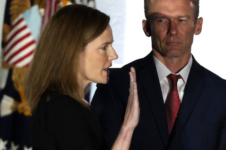 Amy Coney Barrett holds up her right hand and takes the oath as her husband looks on
