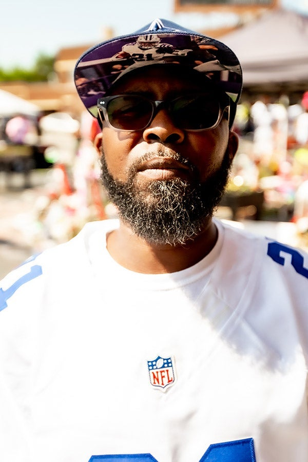 A man in sunglasses and a baseball cap wears an NFL jersey.