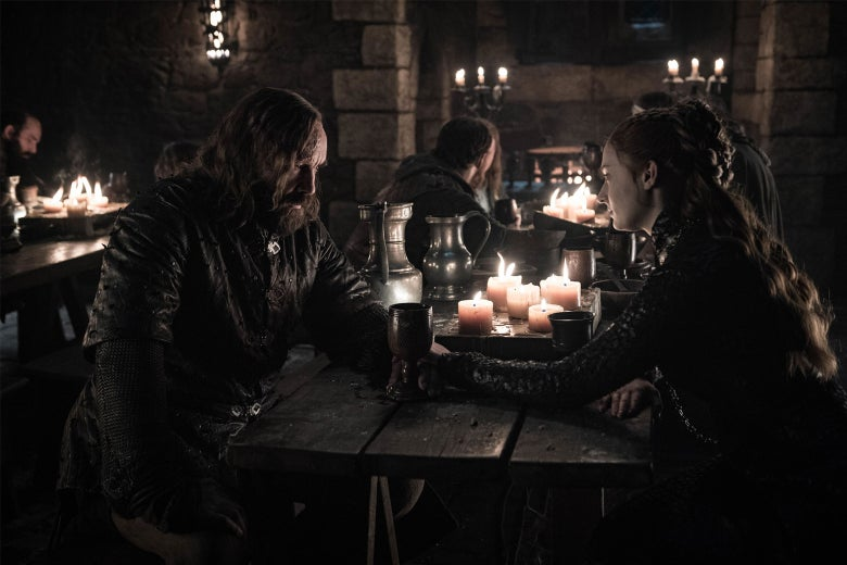 The Hound and Sansa sit across from each other at a table.