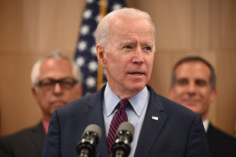 Joe Biden stands in front of two microphones, flanked by men on both sides of him.