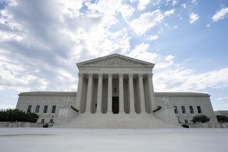 The Supreme Court building against a partly cloudy sky.