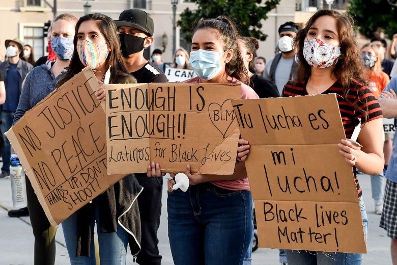 Young Latinos hold up signs in support of Black Lives Matter at a protest