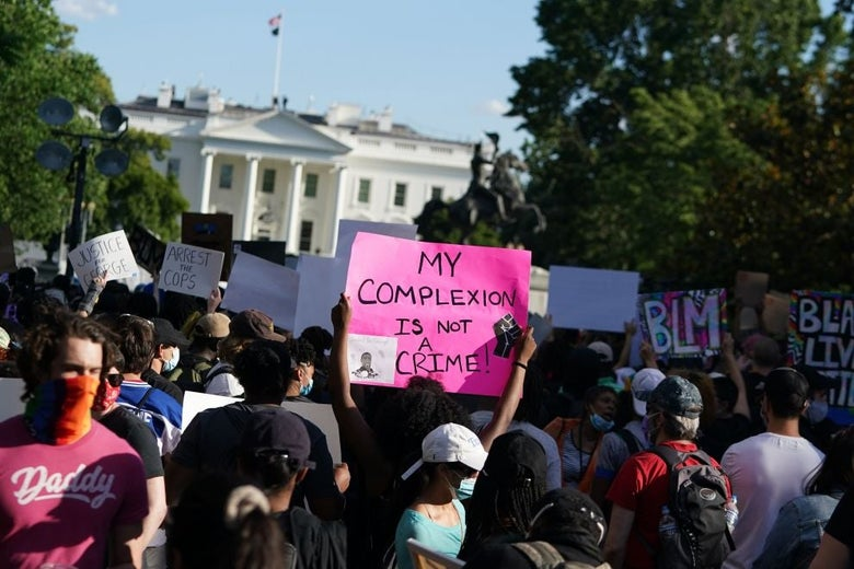 """Protesters hold up signs outside the White House fence. A sign in the foreground says, """"My complexion is not a crime."""""""