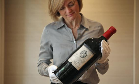 An employee of Sotheby's auction house holds a rare Jeroboam of Chateau Mouton Rothschild from 1953 on Jan. 17, 2012 in London