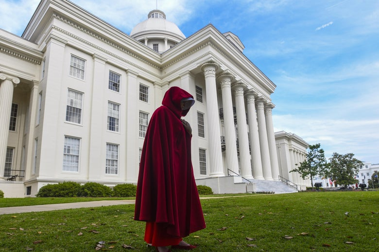 """A protestor dressed as a character from the Hulu TV show """"The Handmaid's Tale,"""" in front of the Alabama statehouse."""