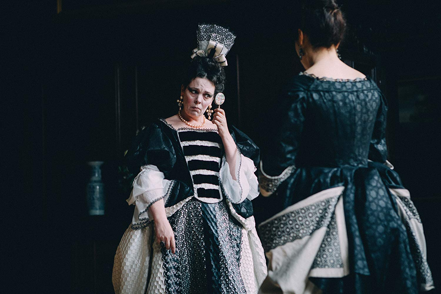 Olivia Colman, in period garb, peers into a tiny mirror.
