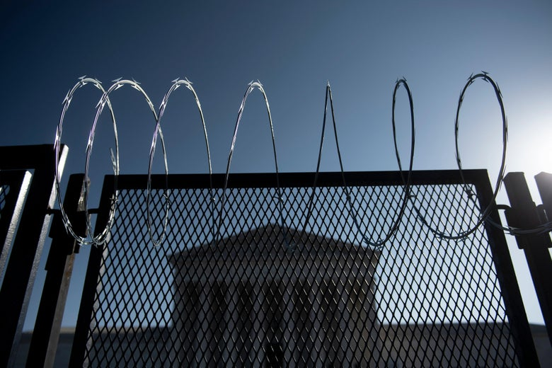 The Supreme Court surrounded by a fence and barbed wire.