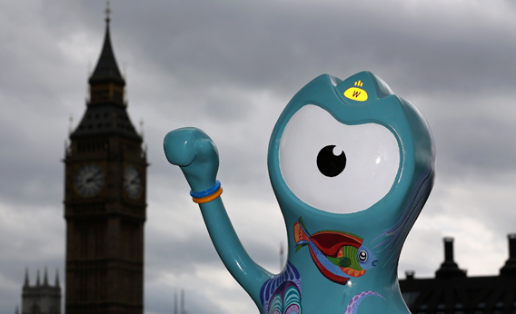 People sit next to a model of a Wenlock, one of the official 2012 Olympic mascots on July 17, 2012 in London, England.