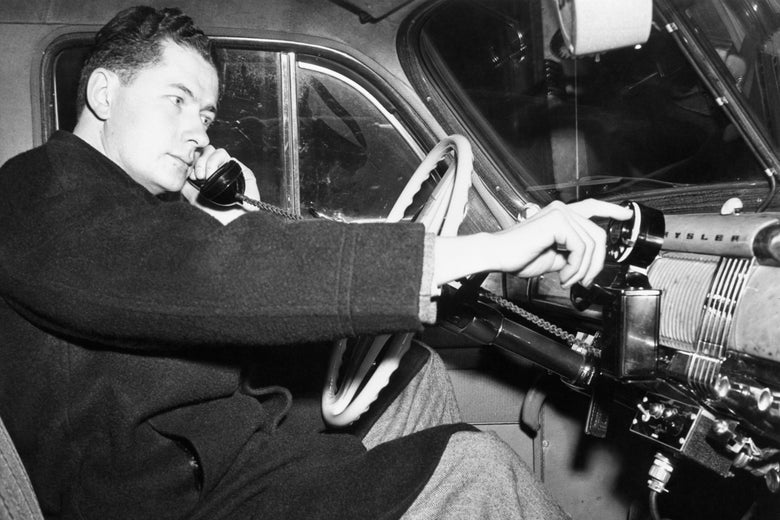 A man sits behind the wheel of a car with a phone to his ear as his finger uses a rotary dial.