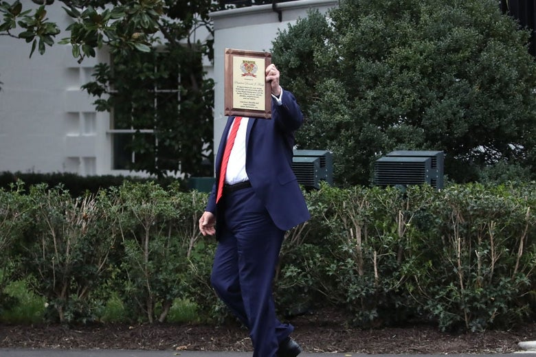 Trump, walking outside the White House, holds a plaque in the air such that it blocks his face.