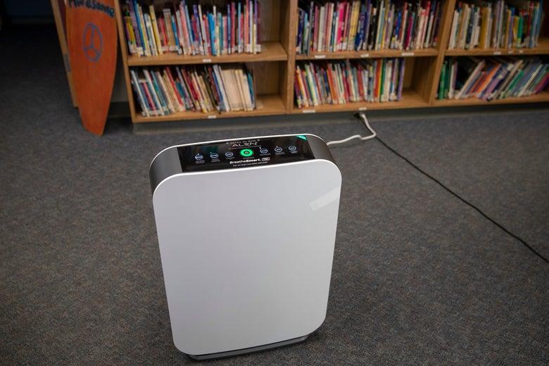 An air purifier is seen in front of a bookshelf.