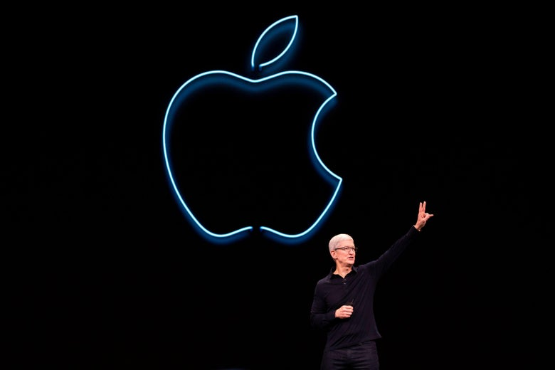 Tim Cook on a stage gesturing in front of a neon Apple logo.