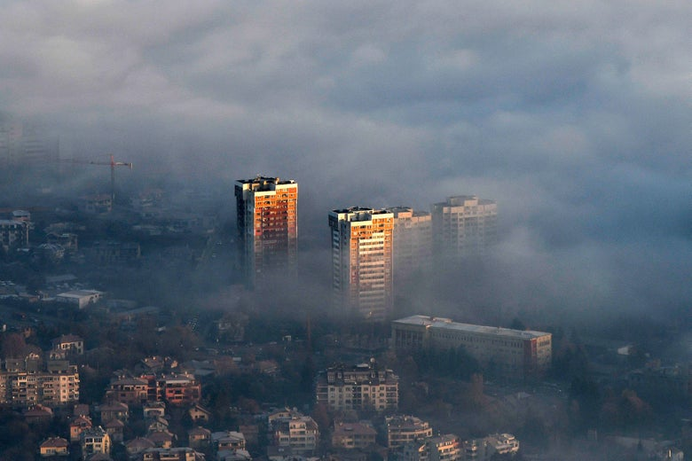 An aerial view of buildings partly obscured by thick smoke and dark clouds