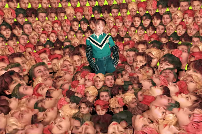 "A member of Korean boyband BTS surrounded by images his own face in the trippy video for ""Idol."""