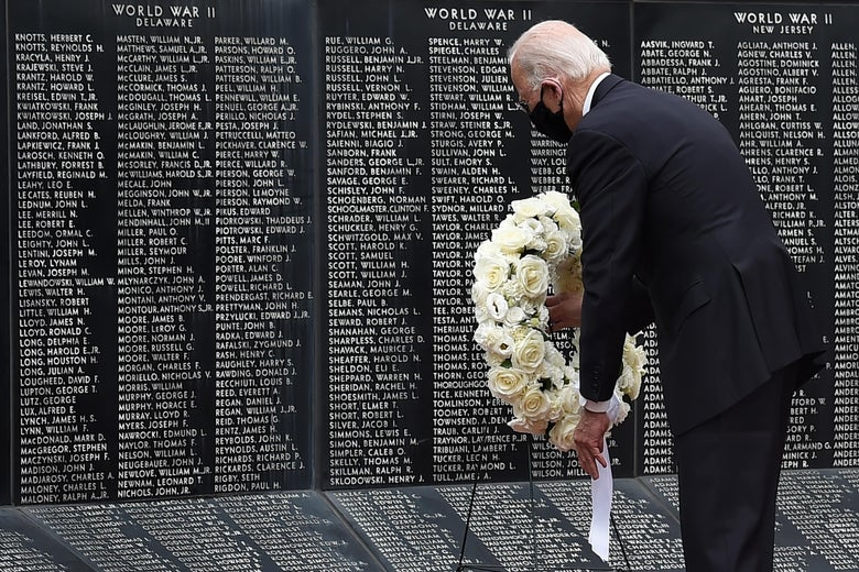 Democratic presidential candidate Joe Biden, wearing a black mask, lays a wreath to pay his respects to fallen service members on Memorial Day.