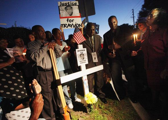 Supporters gather around a cross during a candlelight vigil at a memorial to Trayvon Martin in Sanford, Fla., on March 25, 2012.