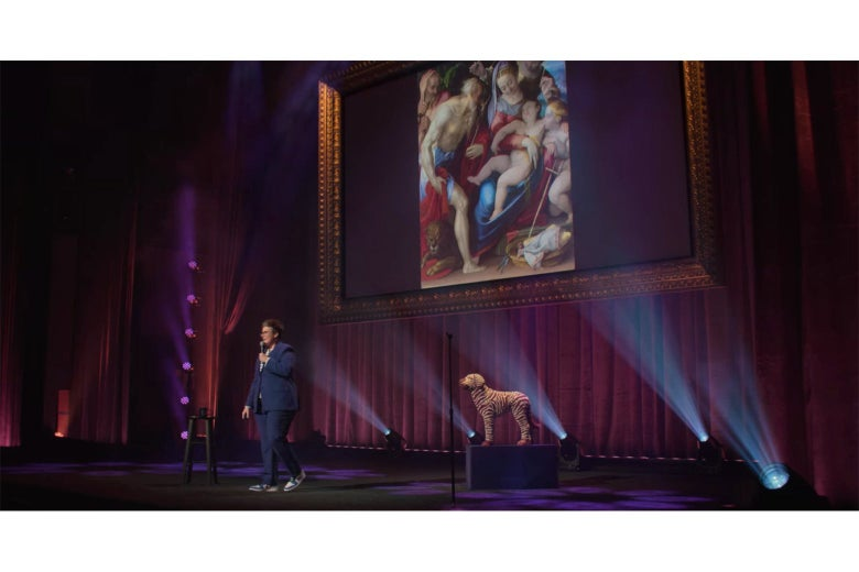Hannah Gadsby onstage in front of a painting of the Holy Family in which the baby Jesus is gigantic for some reason.