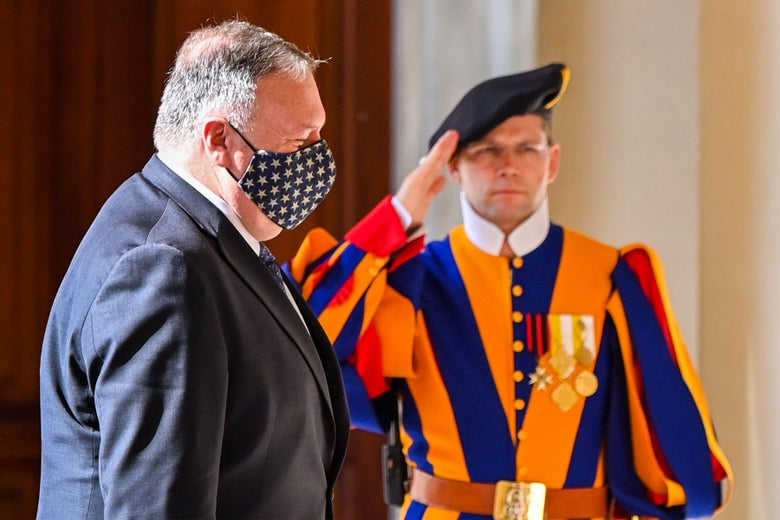 Mike Pompeo, wearing an American flag mask, walks in front of a Swiss Guard raising his arm in salute