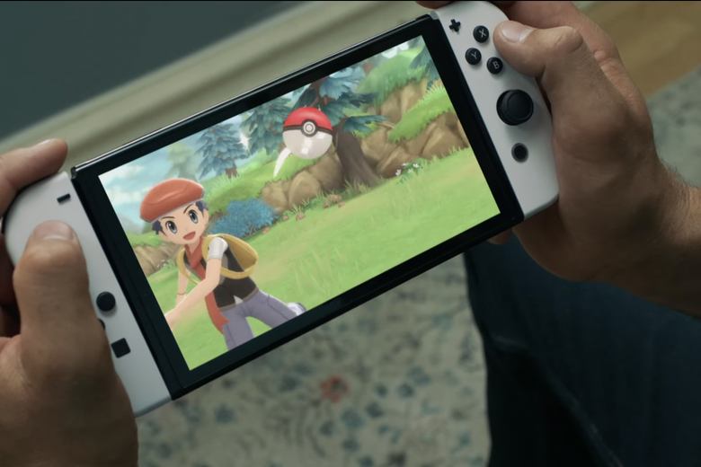 A pair of hands hold a Nintendo Switch console. On the screen is a boy wearing a red beret throwing a red-and-white ball across green grass.