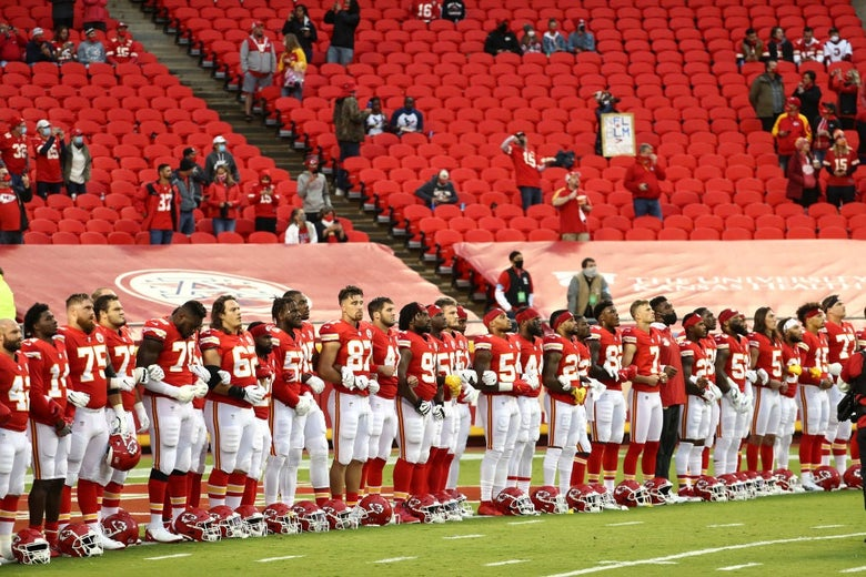 A line of players dressed in the Chiefs' red uniforms stands with locked arms in front of a sparse, socially distanced crowd.