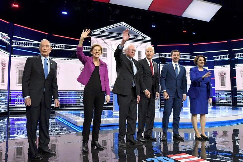 Mike Bloomberg stands off to the side but on the debate stage with Elizabeth Warren, Bernie Sanders, Joe Biden, Pete Buttigieg and Amy Klobuchar in Las Vegas on February 19, 2020.