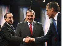 Mike Huckabee and Mitt Romney shake hands before a debate, while Duncan Hunter looks on          Click image to expand.
