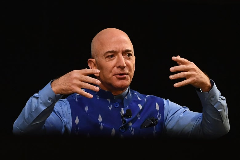 Jeff Bezos gestures with his arms raised against a black background.