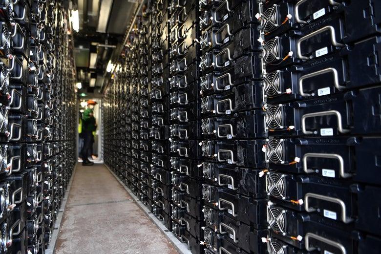 A worker walks through a hall of stored batteries.