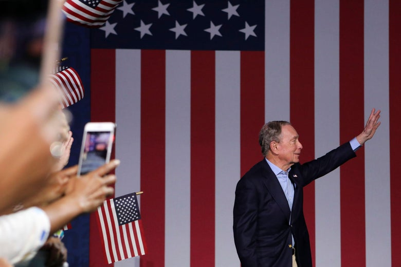 Mike Bloomberg waves in front of an American flag.