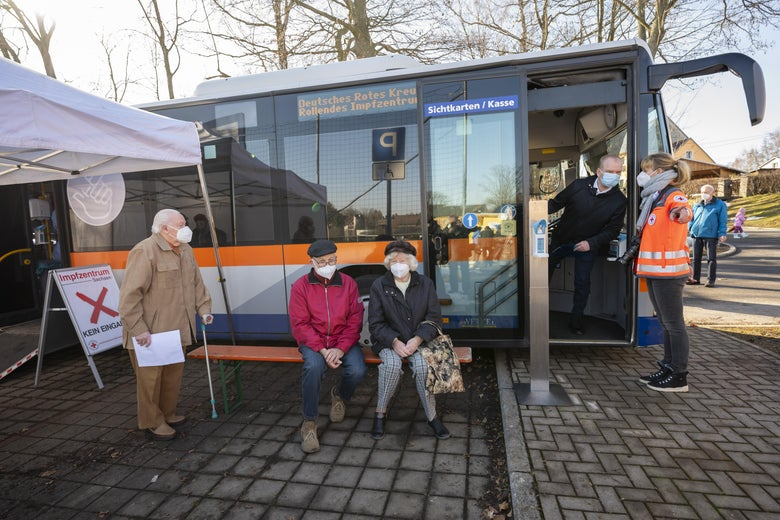 People sit outside a bus turned mobile vaccination unit for Covid-19 shots.
