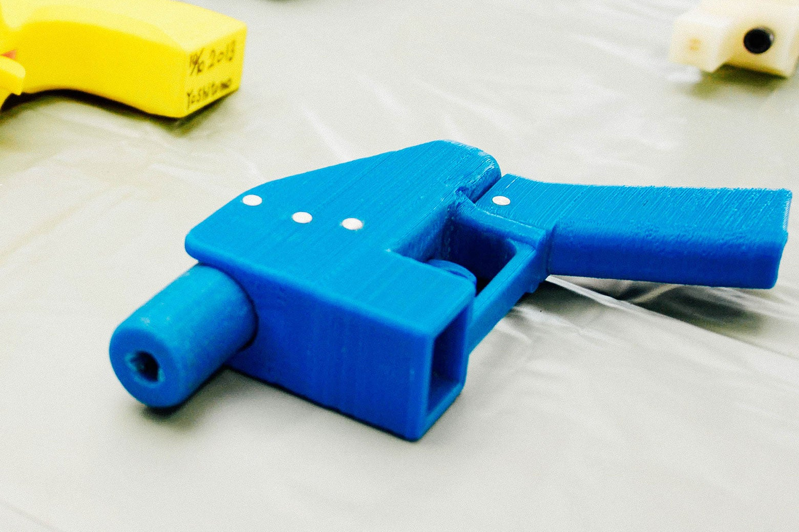 A blue plastic handgun with yellow plastic handguns off to the side.