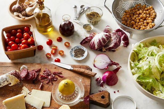 Onions, lettuce, radicchio, tomatoes, chickpeas, and more ingredients strewn about a white marble table top.