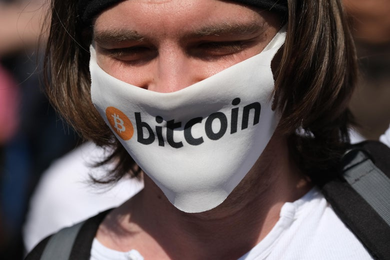 A man wears a mask with the Bitcoin logo .