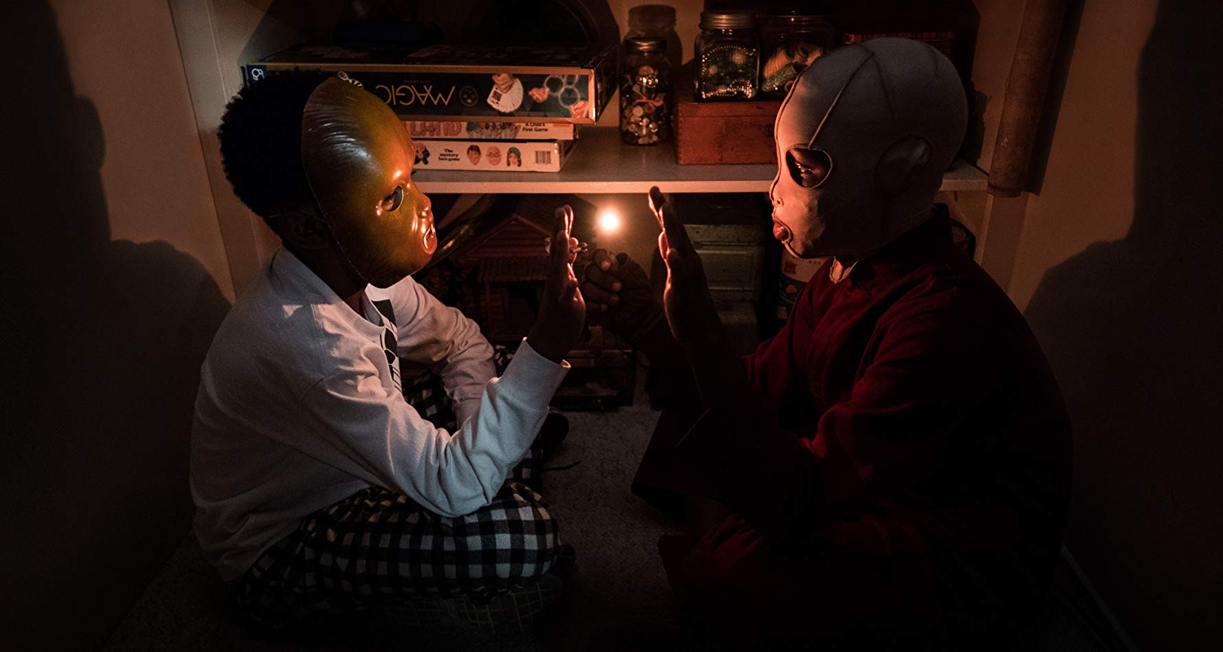 Jason and Pluto sit facing each other in a closet, playing with fire.