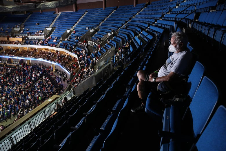 A Trump supporter sits in the upper tier of the arena, which is almost completely empty.