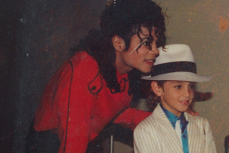 Michael Jackson in a red shirt poses with a child, Wade Robson, dressed in an outfit similar to Jackson's Smooth Criminal persona.