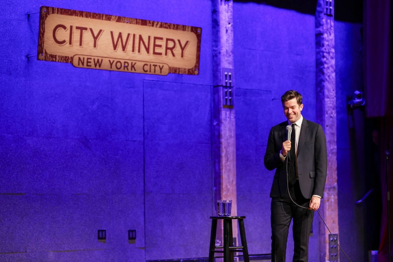A man in a black suit and tie stands next to a stool with a cup of water on top of it. He's on a stage with a purple light behind him and a sign that says CITY WINERY above him.