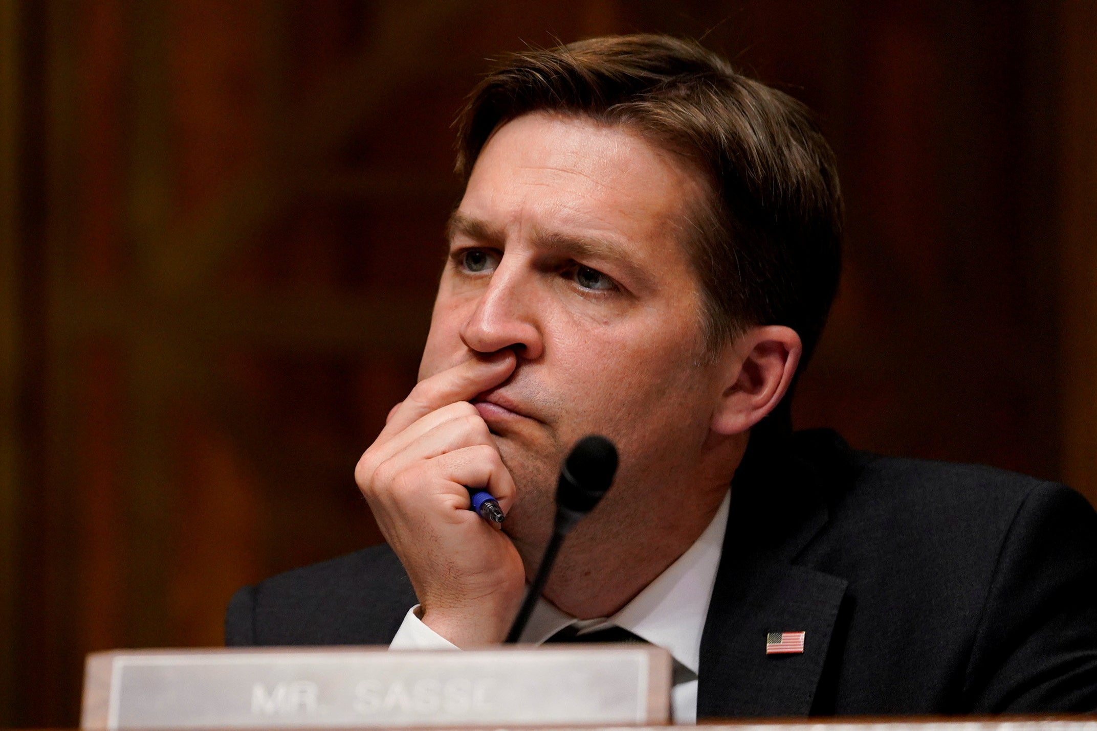 Sasse is shown resting his head on his right hand while watching William Barr's testimony.