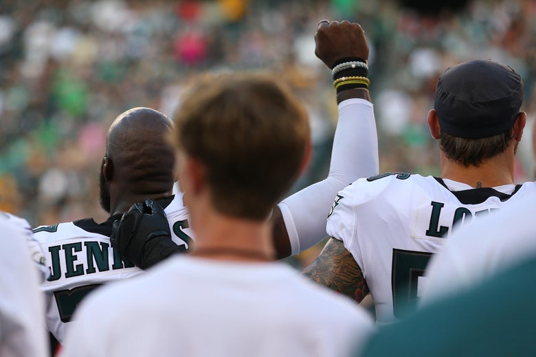 Malcolm Jenkins #27 of the Philadelphia Eagles raises his fist during the national anthem as Chris Long #56 puts his arm around him