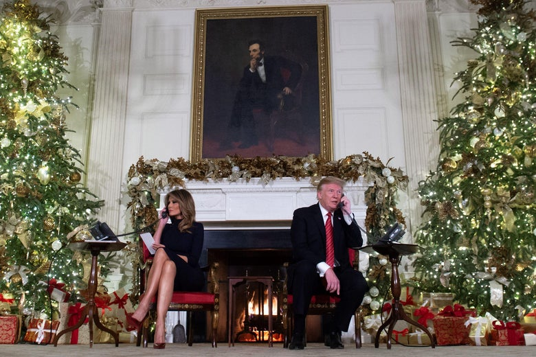 Trump and Melania each sit next to a Christmas tree while speaking on the phone in front of a portrait of Abraham Lincoln.