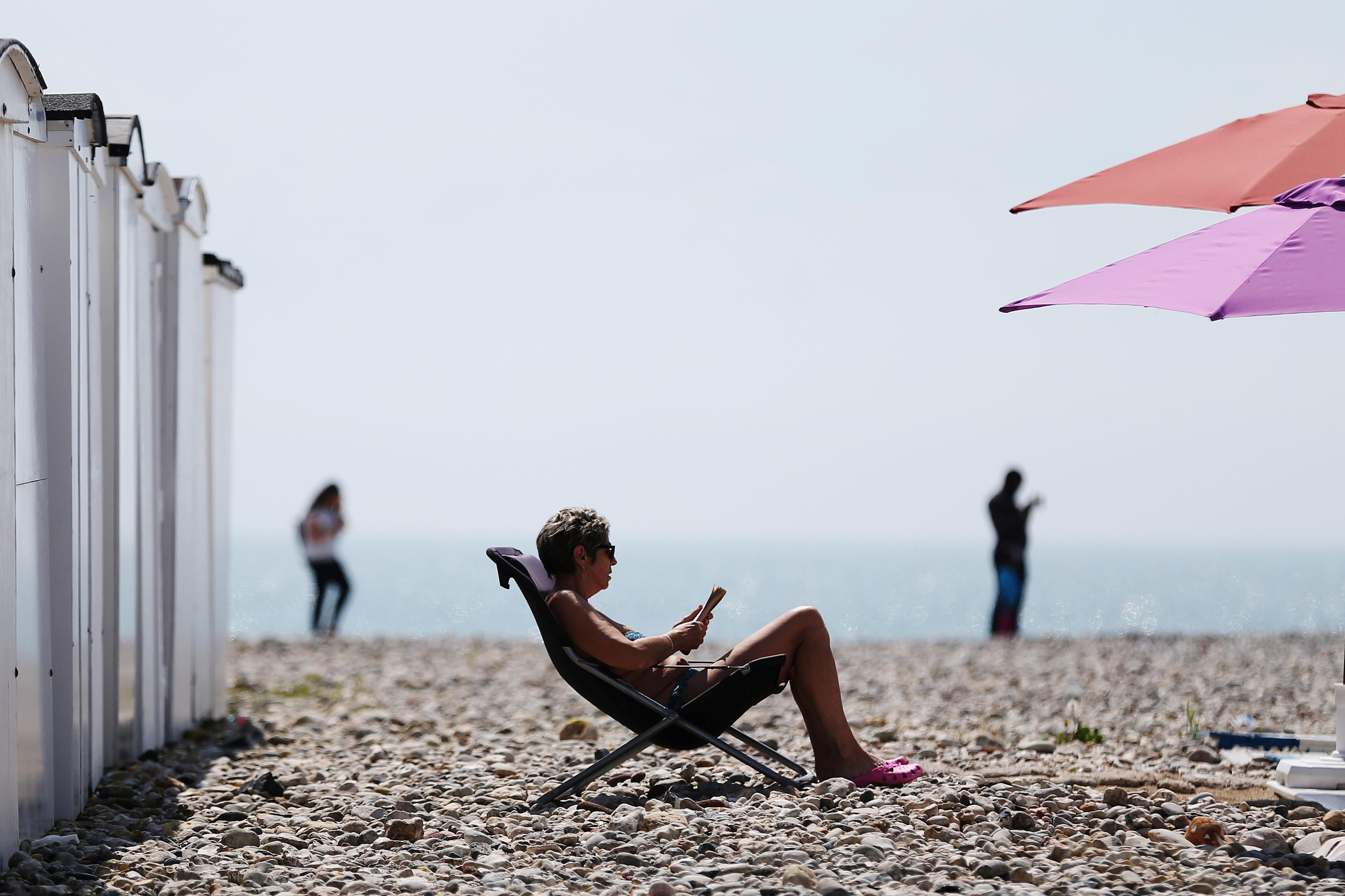 A woman sits on the beach in a deck chair reading on a sunny day in Le Havre, northwestern France, on May 27, 2016.