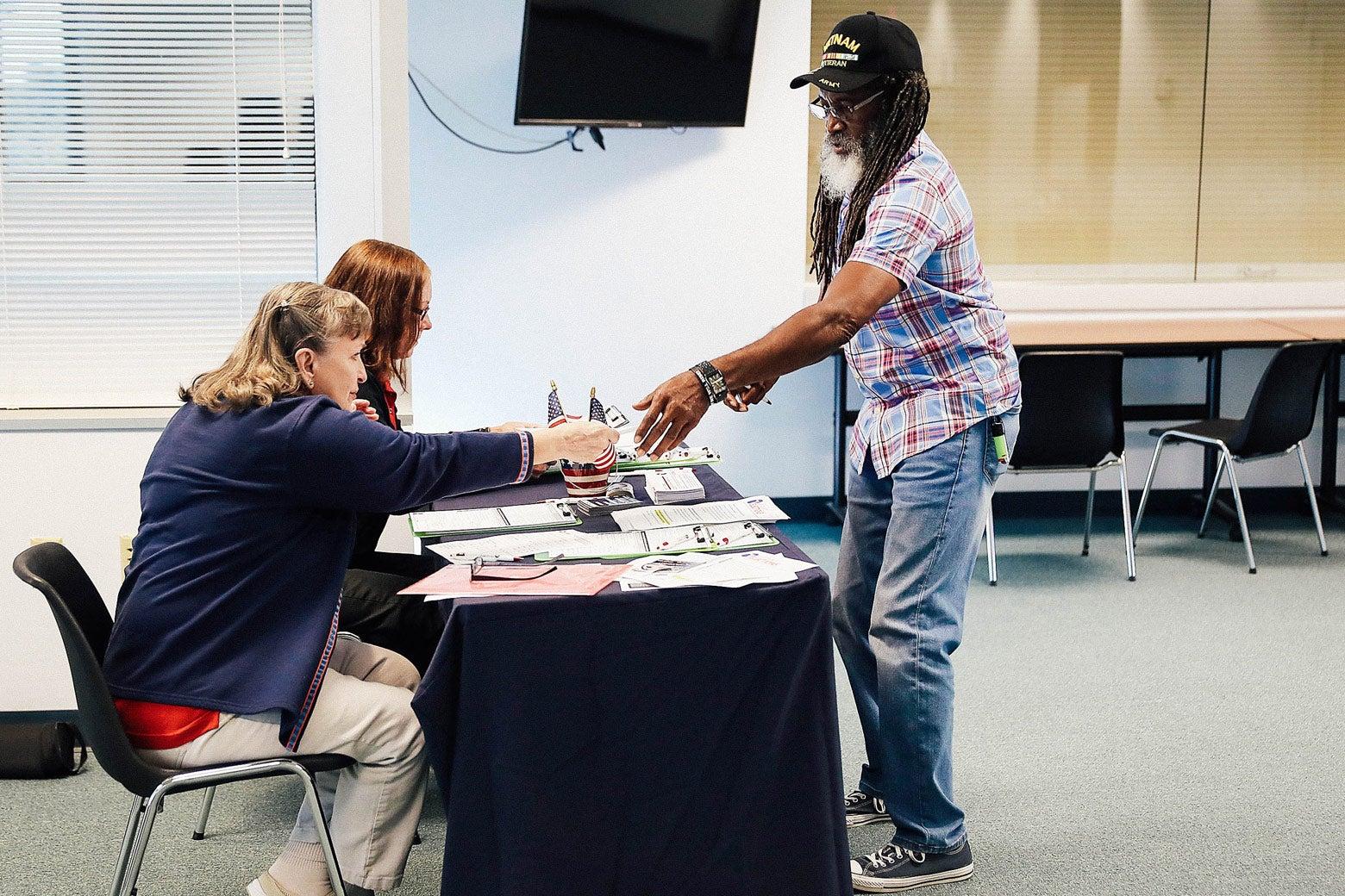 Voter registration workers Rosey Brockamp and Sheryl Podley register Clarence Singleton on Jan. 8 in Fort Myers, Florida.