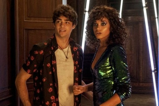 Noah Centineo and Ella Balinska stand next to each other, seen from the waists up, in Charlie's Angels.
