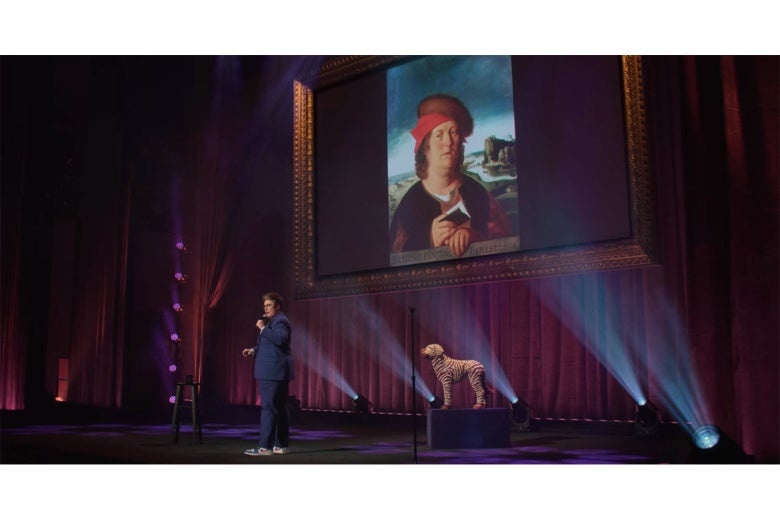 Hannah Gadsby stands in front of a projected image of a portrait of a not-very-bright looking man dressed in red.