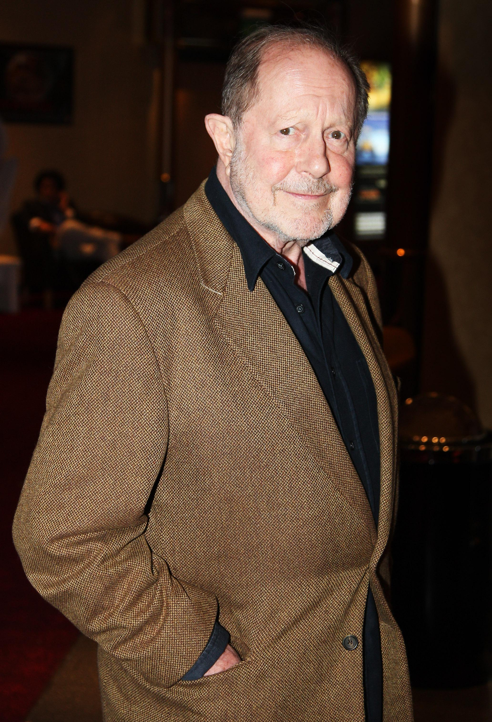 Nicholas Roeg, in a brown jacket and black shirt.