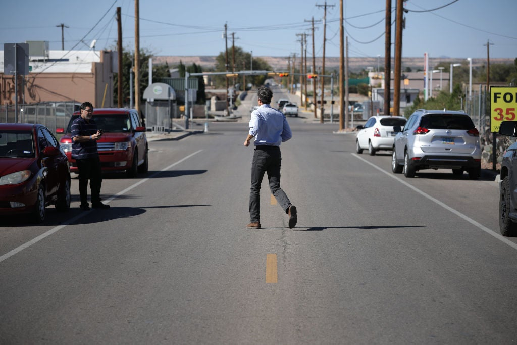 O'Rourke jogs across a two-lane road to greet a voter.