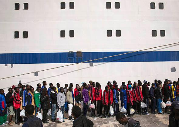 Migrant men wait in line to board a ship bound for Sicily.
